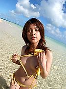 Hot Asian girl in a yellow string bikini takes it all off while walking in the clear water and showing off her hairy patch.