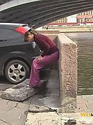 Embarrassed angel peeing in her amazing pants behind a car in public