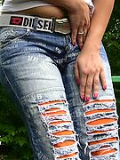 Red miss in the shades piss-drenches her fashion torn jeans outdoors