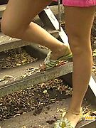 Pink mini skirt and panties of a fair woman pissed on the park stairs